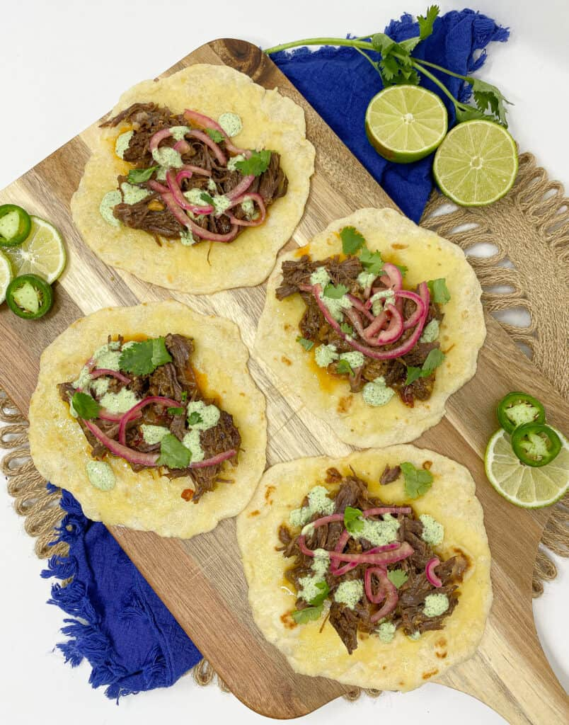 I shredded my short rib barbacoa. I stuffed it in tacos. Lastly, I finished them with jalapeño lime crema, pickled onions, cilantro, and cheese.