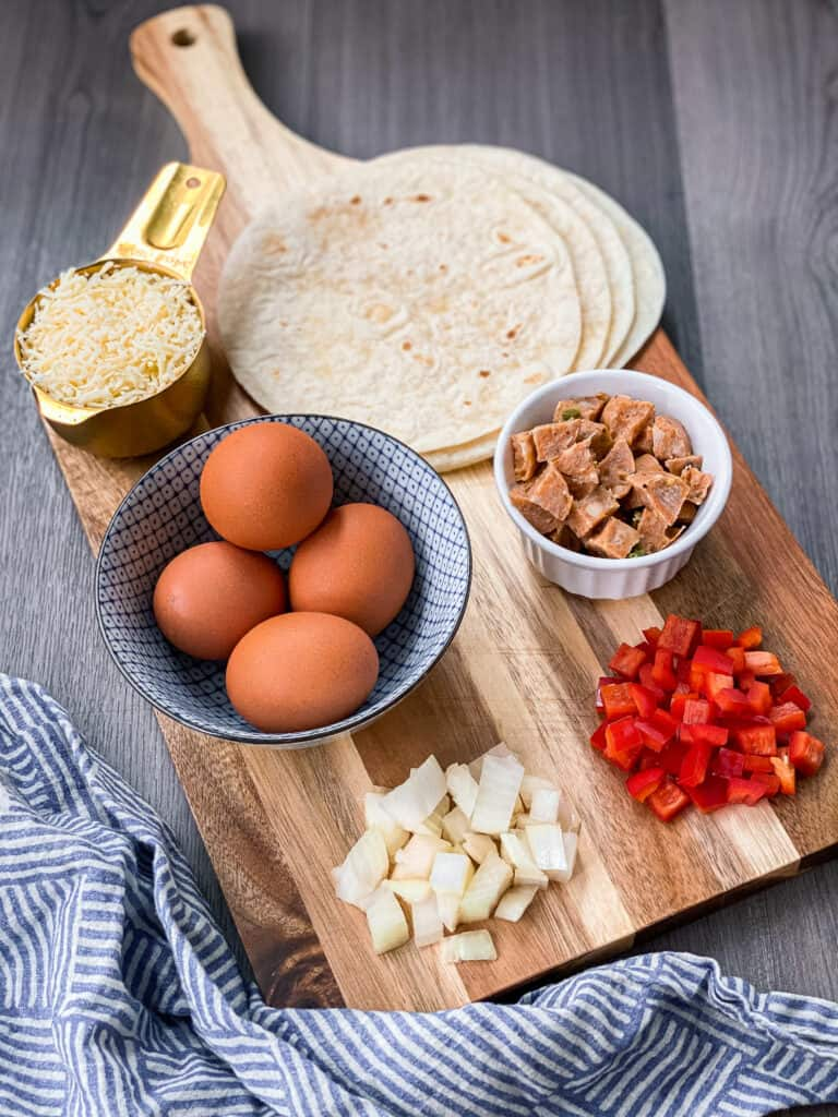 You will need 4 eggs, onions, peppers, sausage, cheese, and tortillas for this recipe.