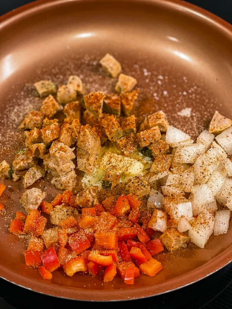 The butter, onions, peppers, chicken sausage, and spices are cooking.