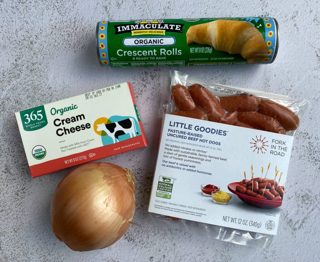 ingredients for pigs in a blanket - crescent rolls, hot dogs, onion, cream cheese