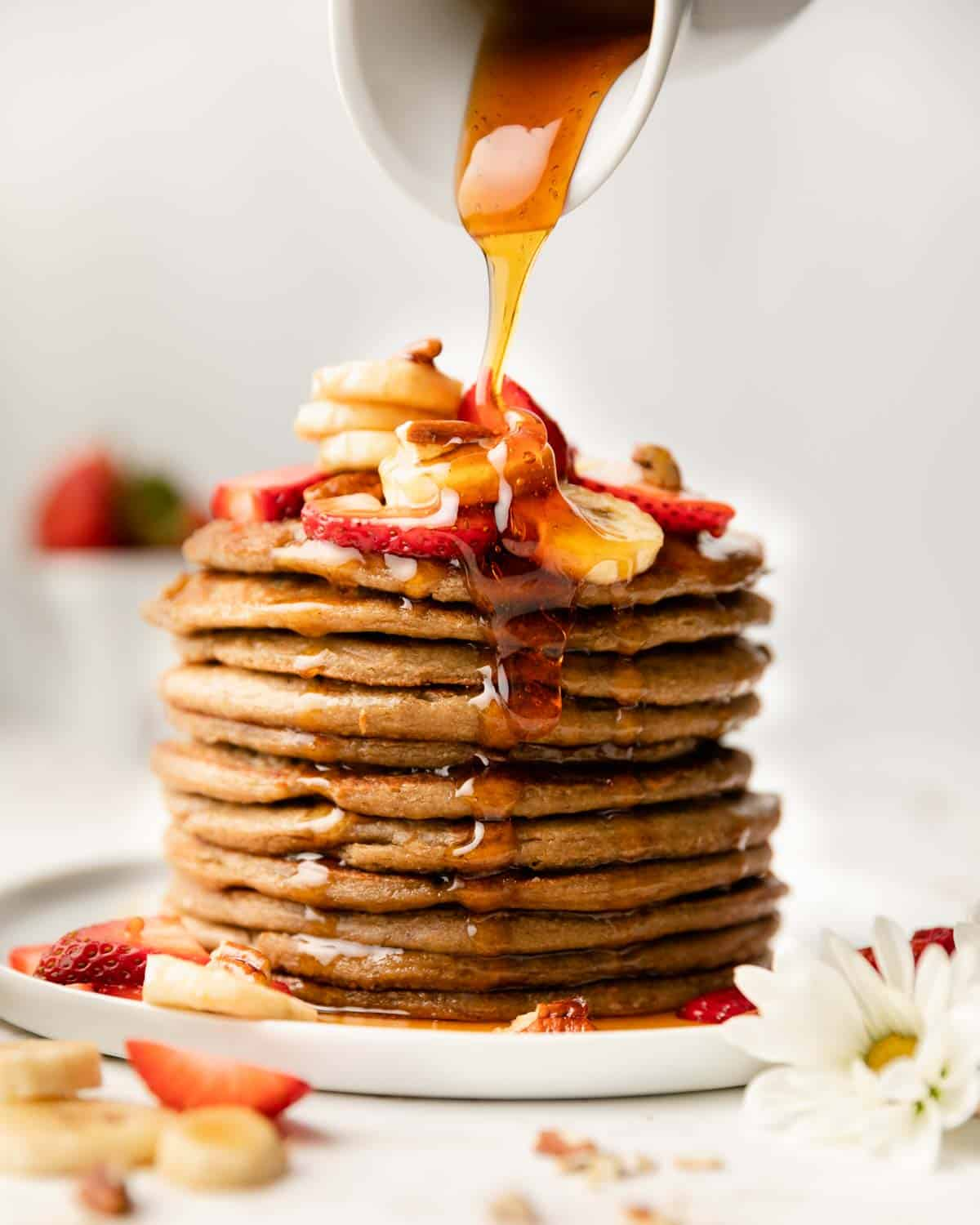 stack of pancakes with syrup being poured on top