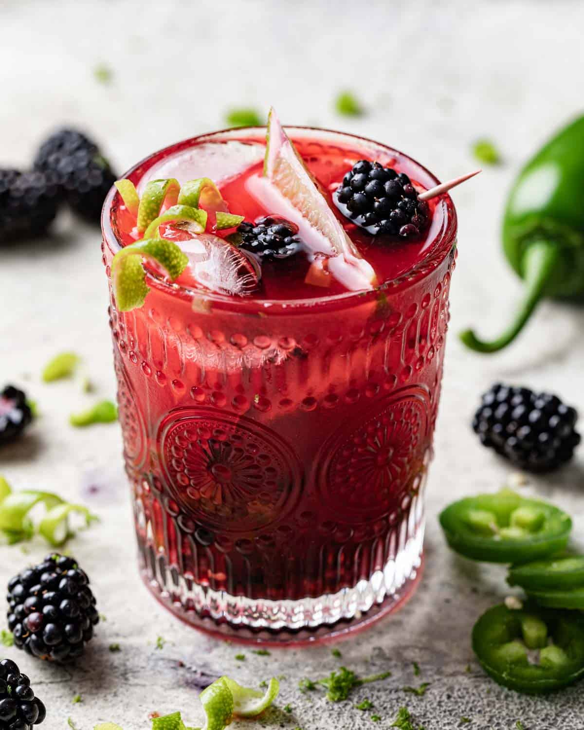 closeup of margarita garnished with lime and blackberry