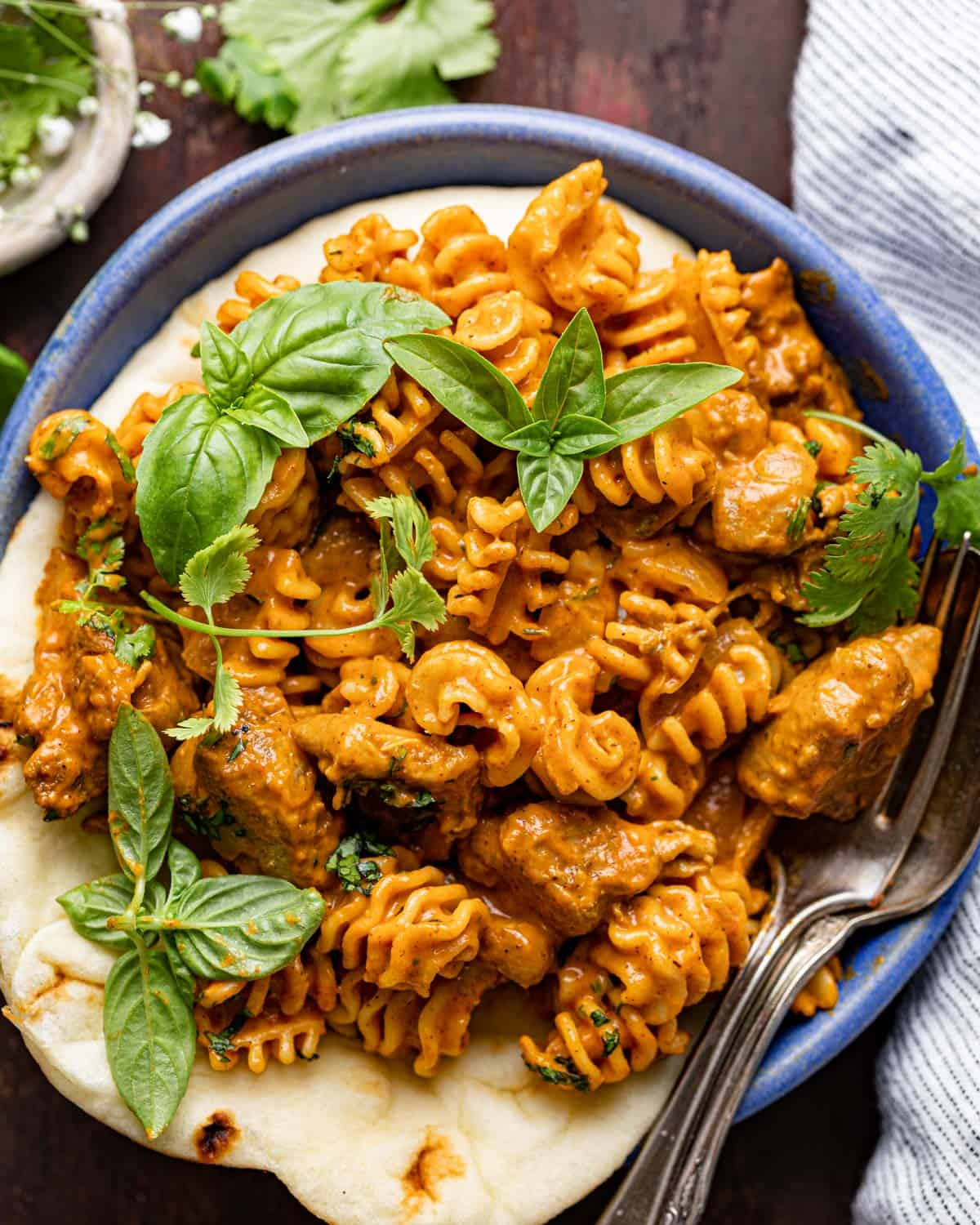 closeup on butter chicken pasta in a bowl with naan