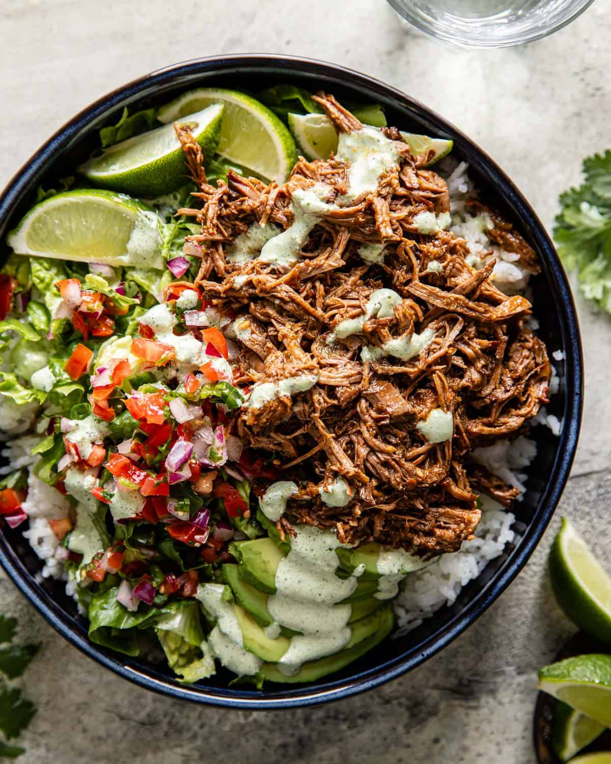 overhead of instant pot shredded beef over rice with pico and lettuce